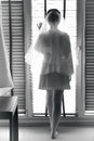 Black and white photo of sexy bride looking out of window Royalty Free Stock Photo