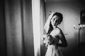 Black white photography beautiful young happy  bride standing near the window Royalty Free Stock Photo
