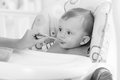 Black and white portrait of adorable baby eating porridge from s Royalty Free Stock Photo