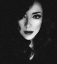 Black and white portrait of a beautiful woman with dark hair curly bright make up Stock Photo