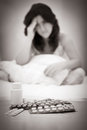 Black white portrait depressed suicidal woman sitting her bed looking pills drugs Stock Image