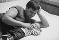 Black and white portrait of father lying on bed with his newborn young baby Stock Images