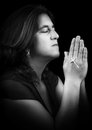 Black and white portrait of an hispanic woman praying holding a small crucifix isolated on with copy space Royalty Free Stock Images