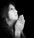 Black and white portrait of a latin woman praying looking up isolated on with copy space Stock Photo