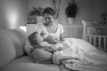 Black and white portrait of mother feeding her baby at night fro Royalty Free Stock Photo