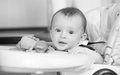 Black and white portrait of smiling baby boy sitting in highchai Royalty Free Stock Photo