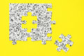 Black and white puzzle pieces on yellow surface Stock Photo