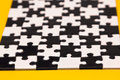 Black and white puzzles on a yellow background Royalty Free Stock Image
