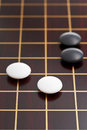 Black and white stones during go game playing on goban close up Stock Photo