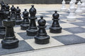 Black and white street chessmen on the chessboard Royalty Free Stock Image