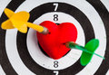 Black white target with two darts in heart love symbol as bullseye closeup of and dart red valentine skeet trap shooting sport Stock Photo