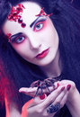 Black widow young woman in dark artistic image posing with spider Stock Photos