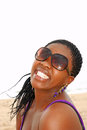 Black woman with fake smile head portrait of an attractive african american young long hair and sunglasses showing her white teeth Stock Images