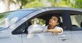 Black woman sitting in car looking out around and checking hair mirror Royalty Free Stock Photography
