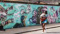 Black woman walking holding her son in front of on a wall decorated in graffiti shoreditch london uk june street art shoreditch Royalty Free Stock Photography