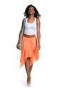 Black woman walking wearing orange skirt on white background Stock Photo