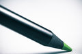 Black wooden green colour pencil drawing on white paper close up with copy space text Royalty Free Stock Photo