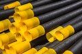 Black yellow plastic drainage pipe pipes and joiners or union couplings stack in a pile waiting usage Stock Image