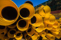 Black yellow plastic drainage pipe pipes and joiners or union couplings stack in a pile waiting usage Royalty Free Stock Photos
