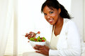 Black young woman eating a green salad Stock Photos