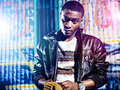 Black youth with jacket and colorful lights potrait photo in front of a graffiti wall Stock Photo