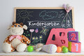 Blackboard in a kindergarten classroom and some baby stuff foam letters cubes hand made drawings Stock Photography