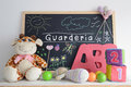 Blackboard in a kindergarten classroom some baby stuff foam letters cubes and hand made drawings the word guarderia spanish word Stock Image