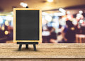 Blackboard menu with easel on wooden table with blur restaurant Royalty Free Stock Photo