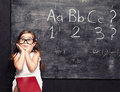 Blackboard squint funny little eyed little girl posing sitting in front of Stock Images
