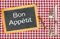 Blackboard with the text bon appetit on a checkered tablecloth Royalty Free Stock Photos