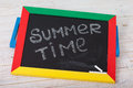 Blackboard with text it's summer time on wooden deck Royalty Free Stock Photo