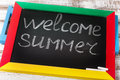 Blackboard with text it's Welcome summer on wooden deck