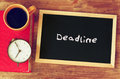 Blackboard with the word deadline written on it, clock and coffee cup over wooden board Royalty Free Stock Photo