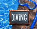 Blackboard with the words diving and swim mask snorkel on a background of water Stock Images