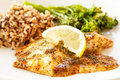 Blackened tilapia with wild rice and broccoli a fillet of fish topped herbs a lemon wedge served couscous broccolini Royalty Free Stock Image