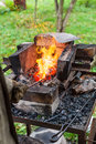 Blacksmith heats iron rod in forging furnace Royalty Free Stock Photo