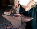 Blacksmith making horseshoes horseshoe on an anvil in the forge and the hands of a at work Royalty Free Stock Image