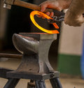 Blacksmith with red iron horseshoe Royalty Free Stock Image