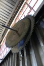 Blades two large circular saw hang suspended from a hook on the side of a corrugated wall at a timber mill Stock Image