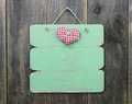 Weathered pink welcome sign with flower heart hanging on wooden door
