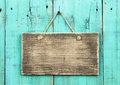 Blank antique wood sign hanging on distressed blue green wooden door