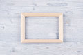 Blank beige wood frame on light blue wooden board. Copy space, top view. Royalty Free Stock Photo