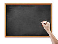 Blank black board and hand with piece of chalk Stock Photos
