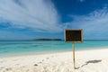 Blank black board on tropical beach background.