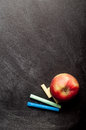 Blank black chalkboard with chalk and apple Stock Image