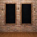 Blank chalkboard on brick wall with glowing light bulbs