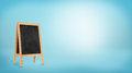 A blank chalkboard stand with a wooden frame on blue background. Royalty Free Stock Photo