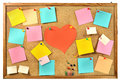 Blank colorful paper notes , office supplies and red paper heart on cork message board. Royalty Free Stock Photo