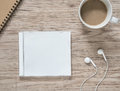 Blank compact disc earphones notebook and coffee on wooden table top view of cd with cover Stock Photos