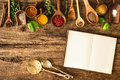 Blank cookbook and spices on wooden table Royalty Free Stock Photos